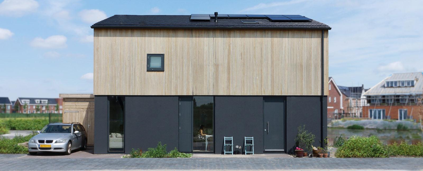 Voorgevel woning Westergouwe te Gouda met donker stucwerk en duurzame houten bekleding
